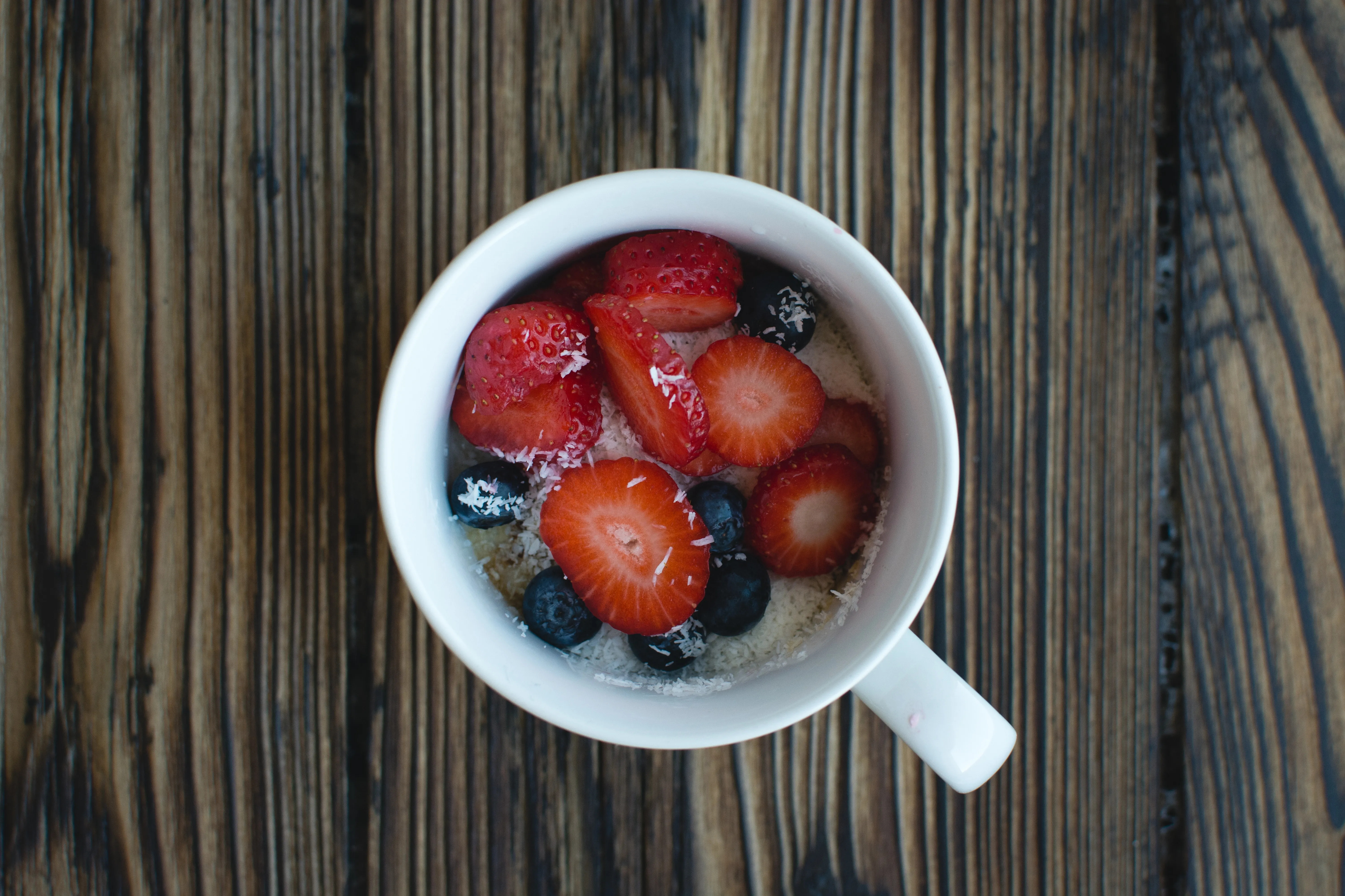 Cup of oatmeal with berries and coconut