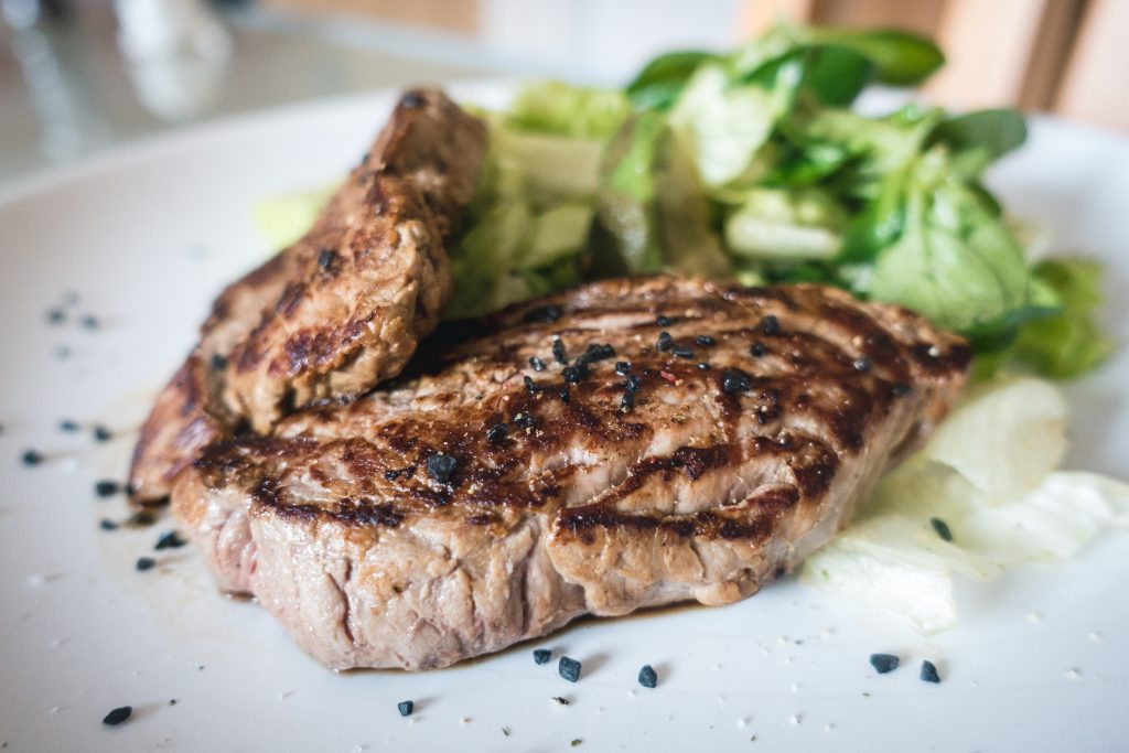 Beef steak with green salad close up