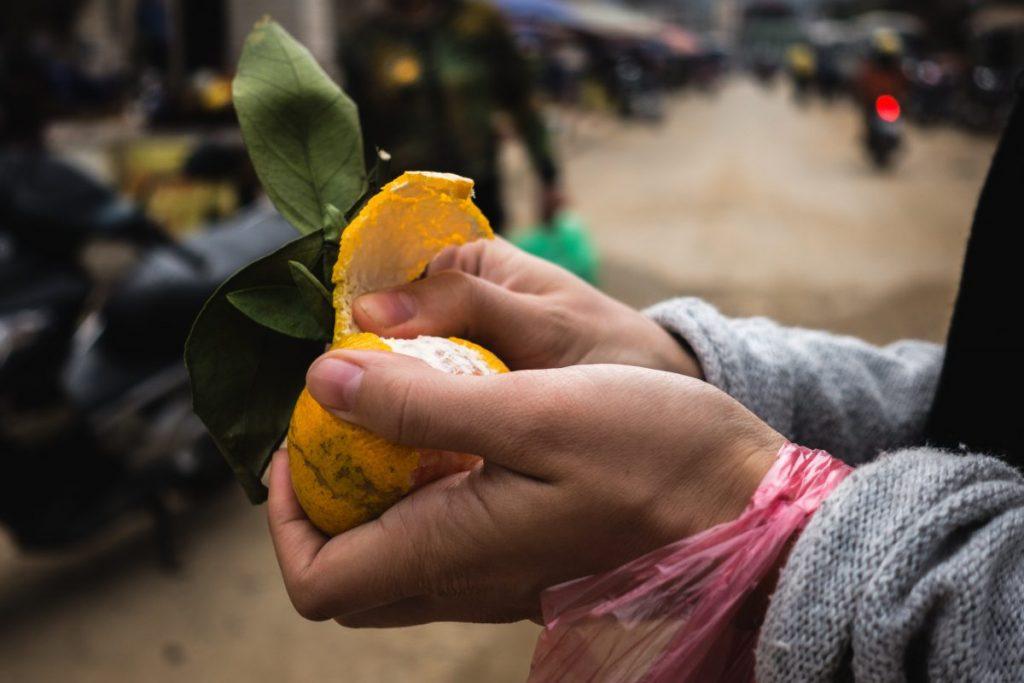 Girl peeling tangerine