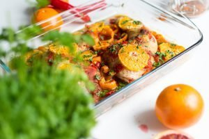 Chicken legs with tomatoes, peppers and oranges