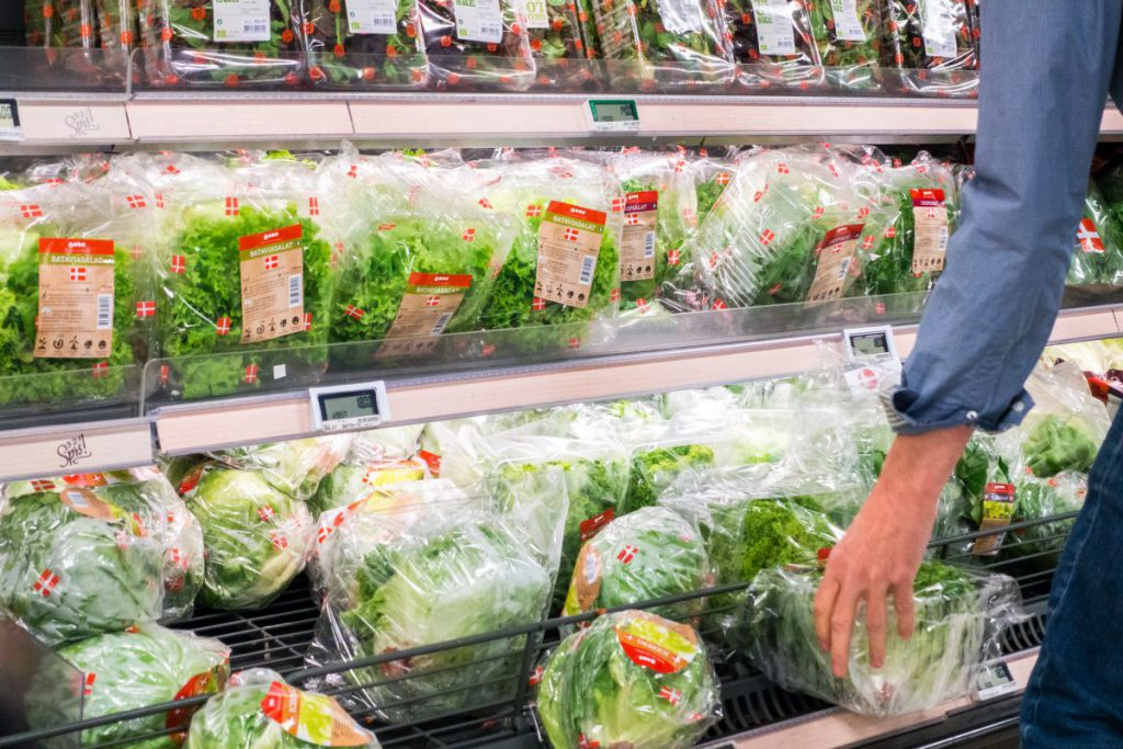 Woman picking lettuce in a grocery store