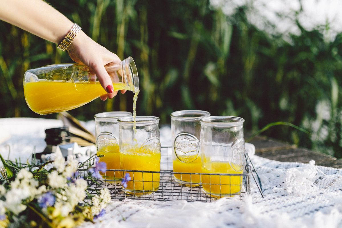 Pouring orange juice on picnic