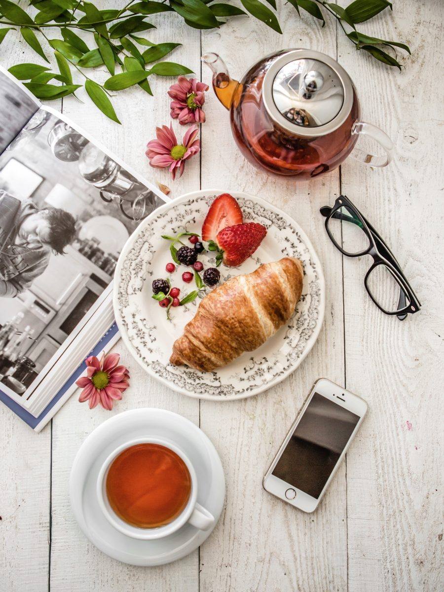 Relaxing with book, tea, croissant and berries
