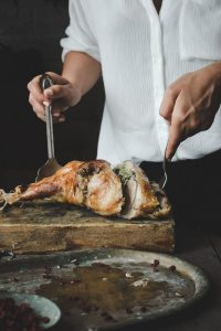 Woman cutting turkey thigh