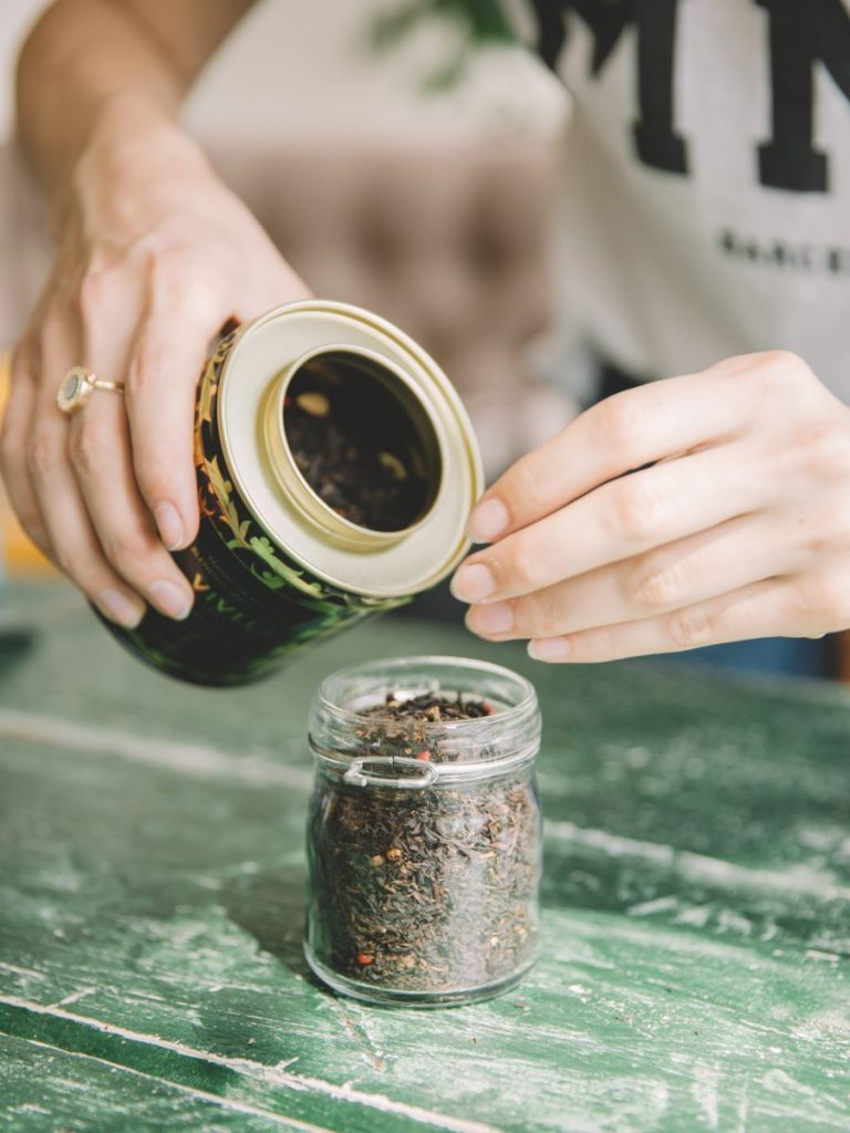 Woman filling glass container with tea leafs