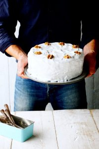 Man holding carrot cake with icing
