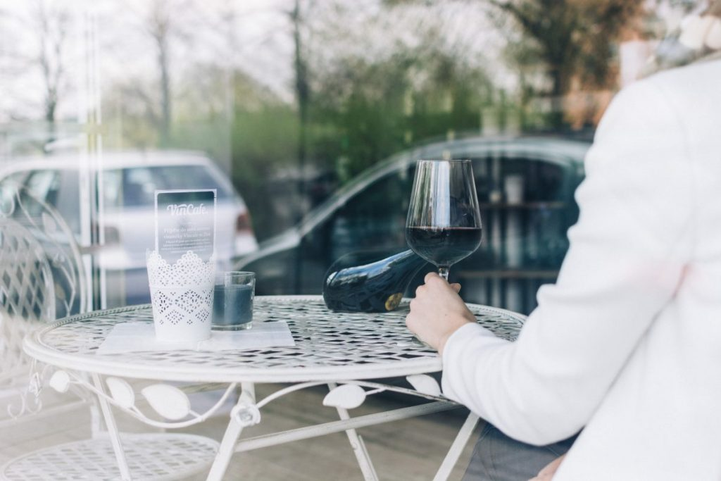 Woman drinking red wine behind a window