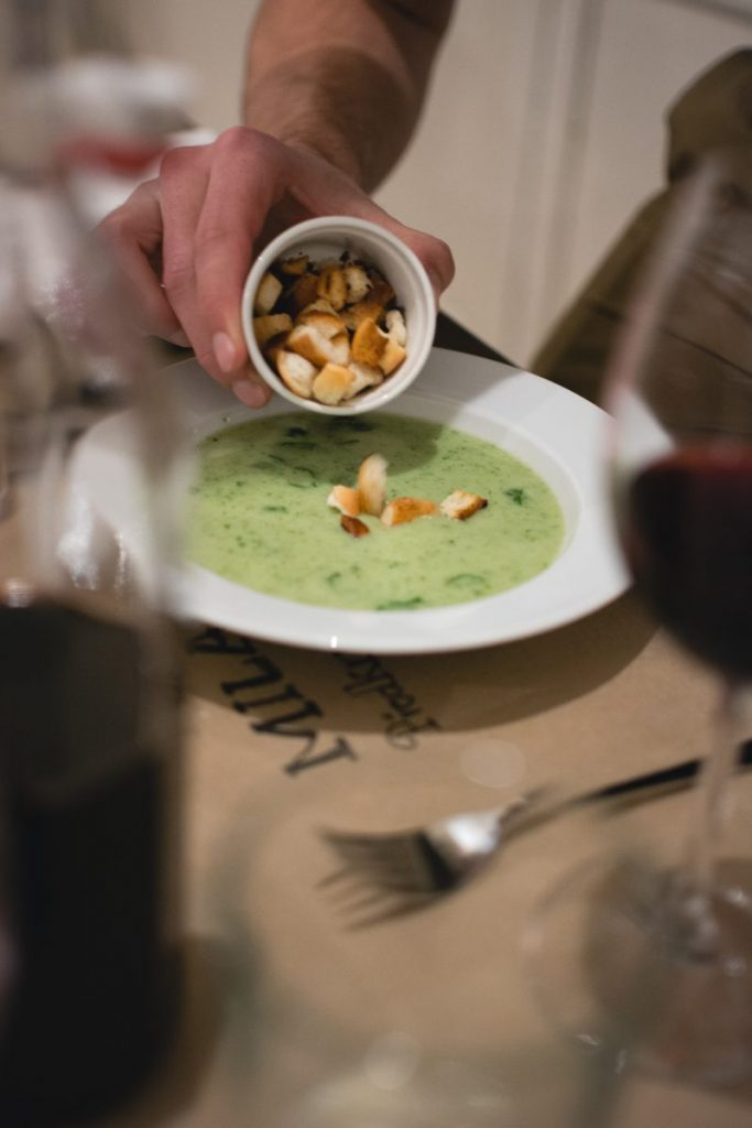Putting croutons in a spinach soup