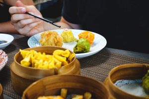 Eating Chinese steamed and fried dim sum with chopsticks