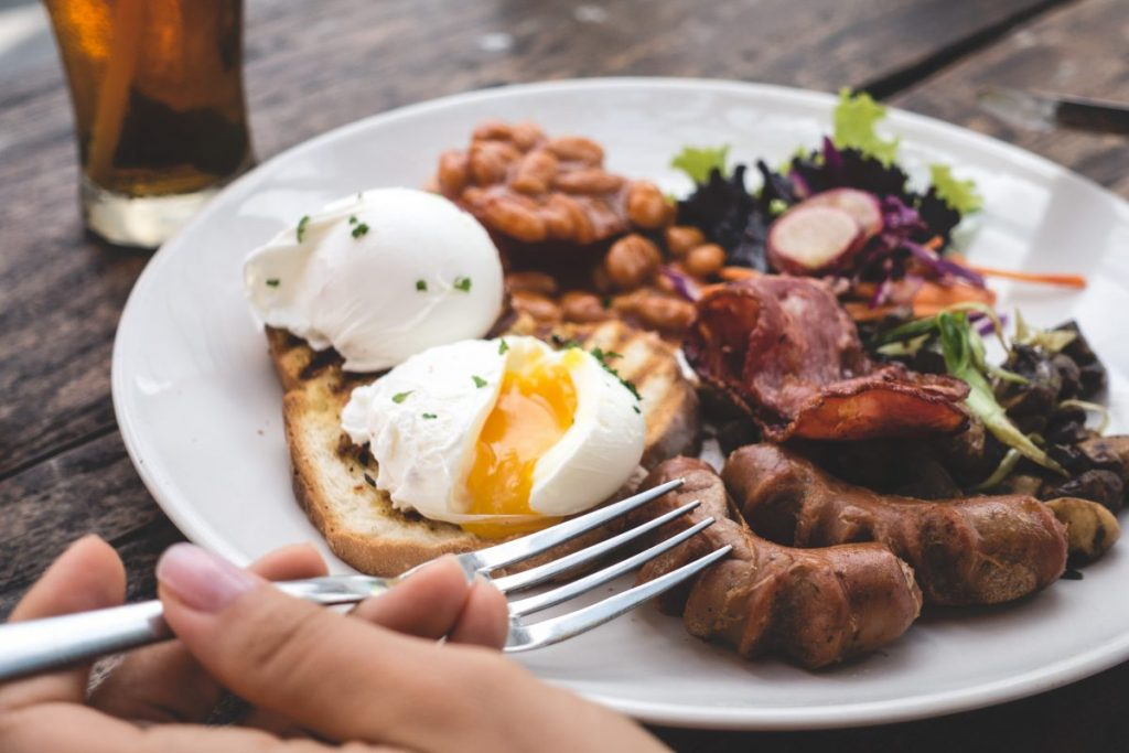 Eating high protein brunch with poached eggs, beans and bacon