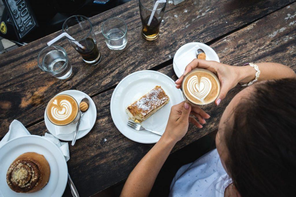 Girl treating herself with flatwhite coffee and cake