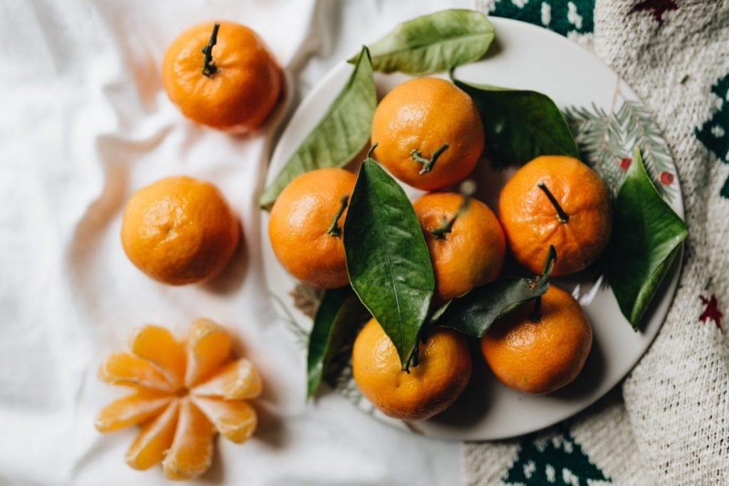 Tangerines with leaves on a white linen