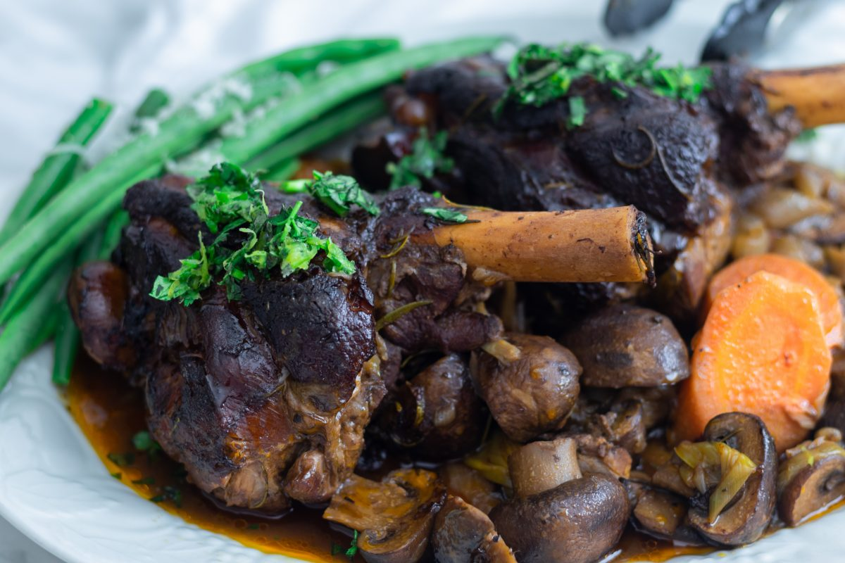 Rosemary lamb shanks with mushrooms and vegetables on wine