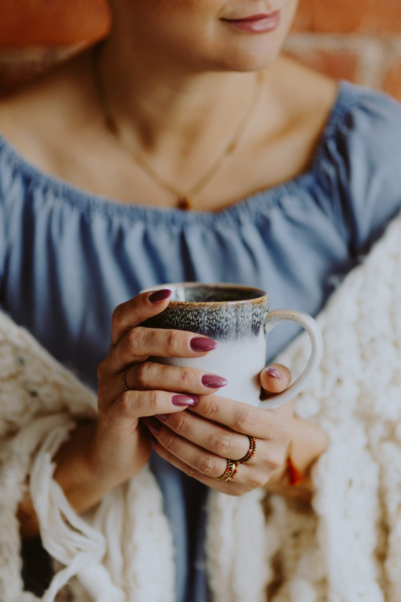 Woman in a warm blanket holding a cup of coffee