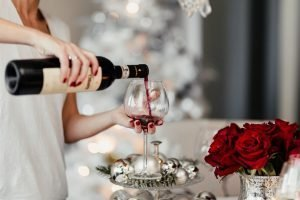 Woman pouring red wine in a glass