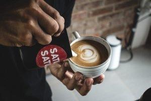 Barista making a perfect latte art on flatwhite