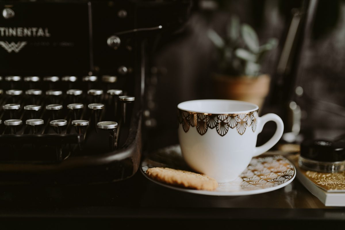 Writing on a typewriter with coffee and biscuit