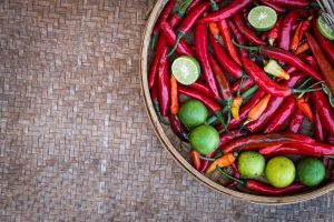 Chili peppers and limes on a wooden table