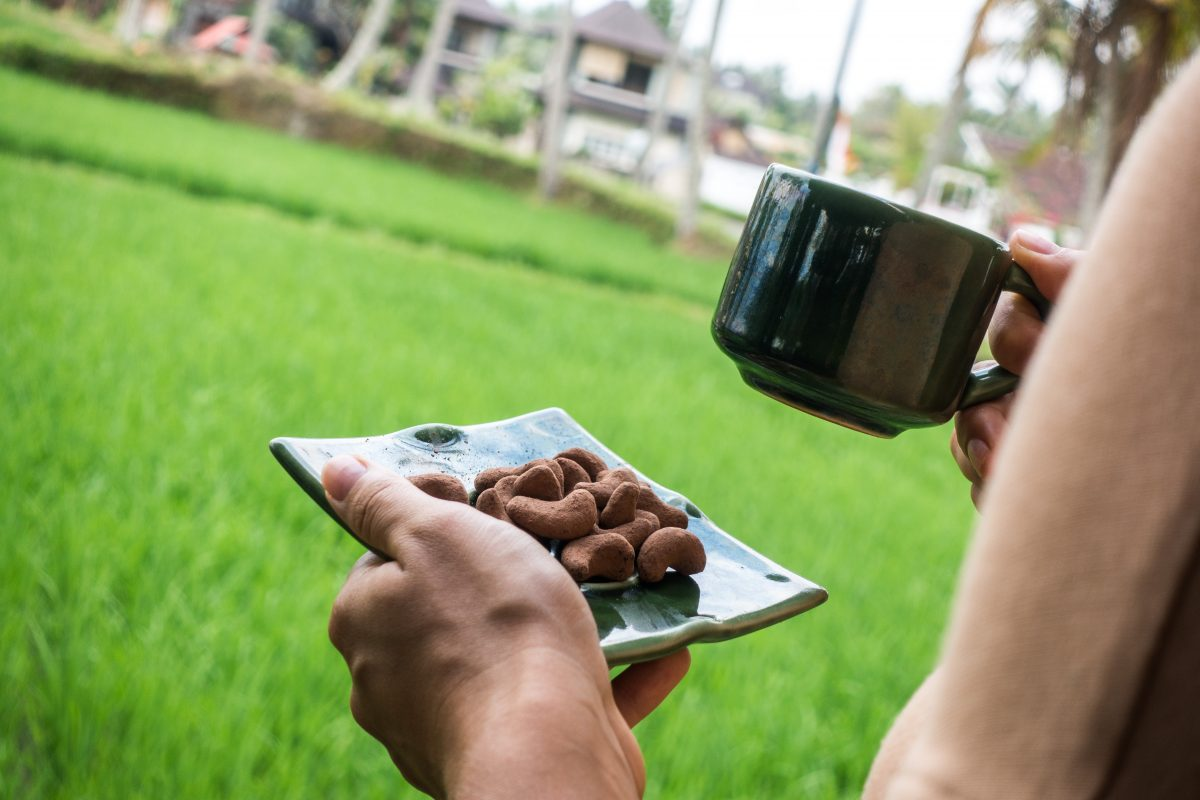 Girl holding a cup of coffee and chocolate coated cashew nuts
