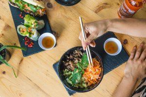 Girl eating Vietnamese food with chopsticks