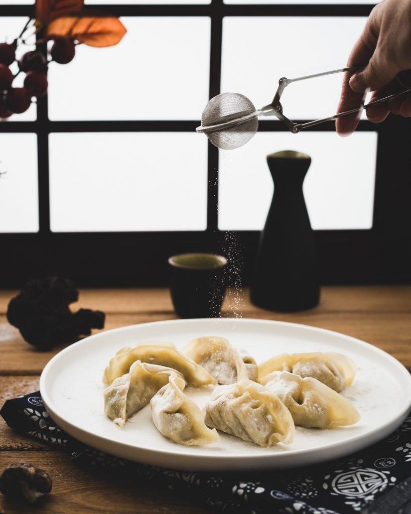 Spreading sugar on sweet fruity dumplings