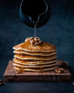 Pouring honey on pancakes with walnuts