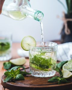 Pouring water in a glass with mint and lime