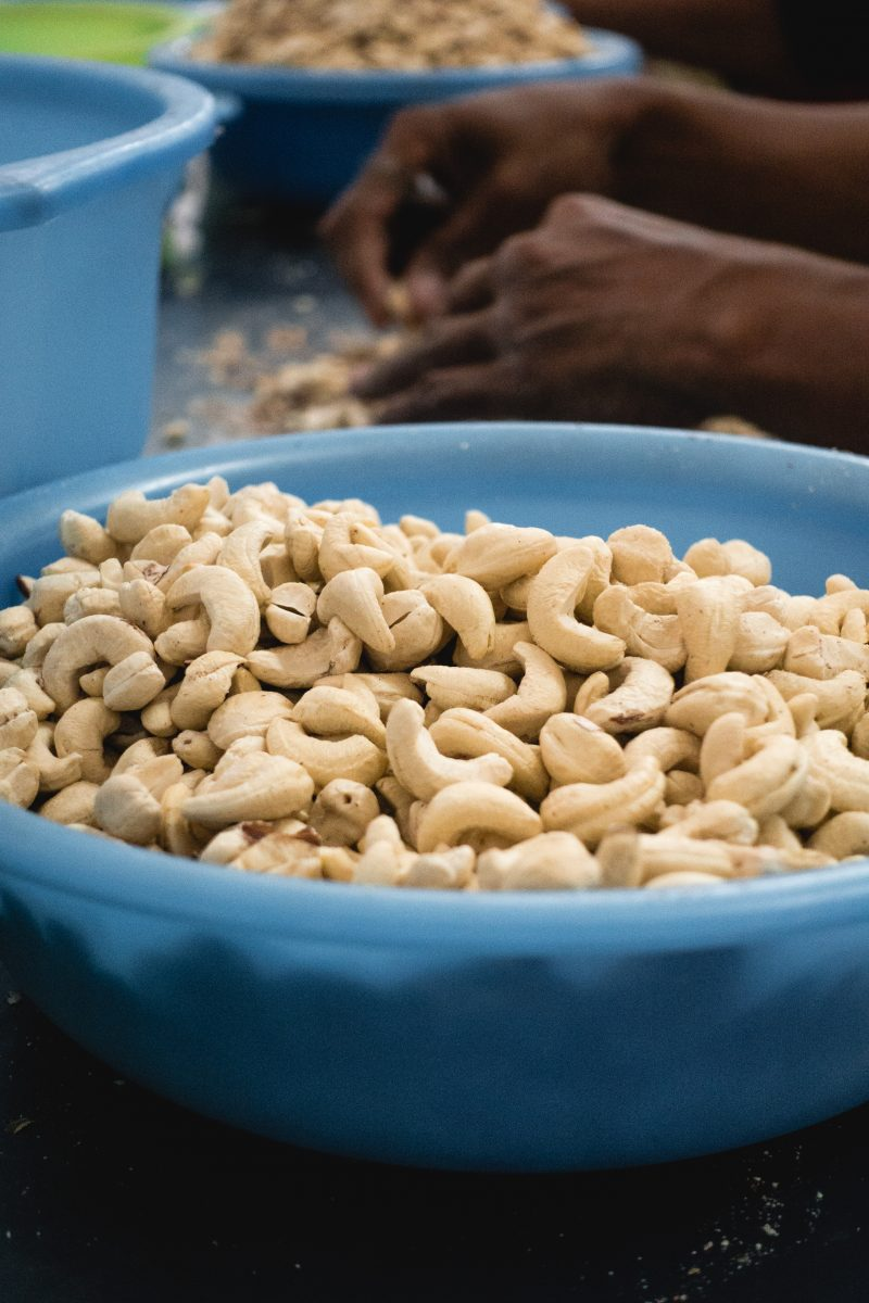Woman peeling cashew nuts