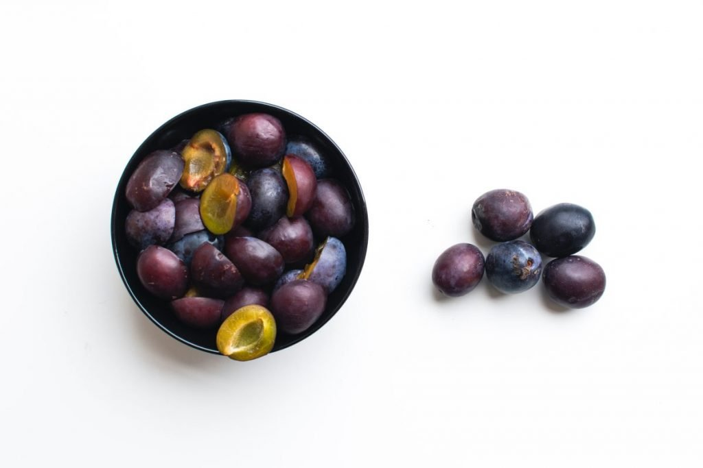 Aerial shot of fresh organic plums on a white background