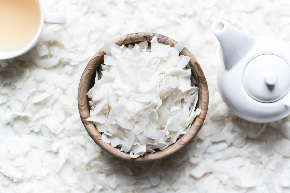 Coconut flakes in a wooden bowl with tea