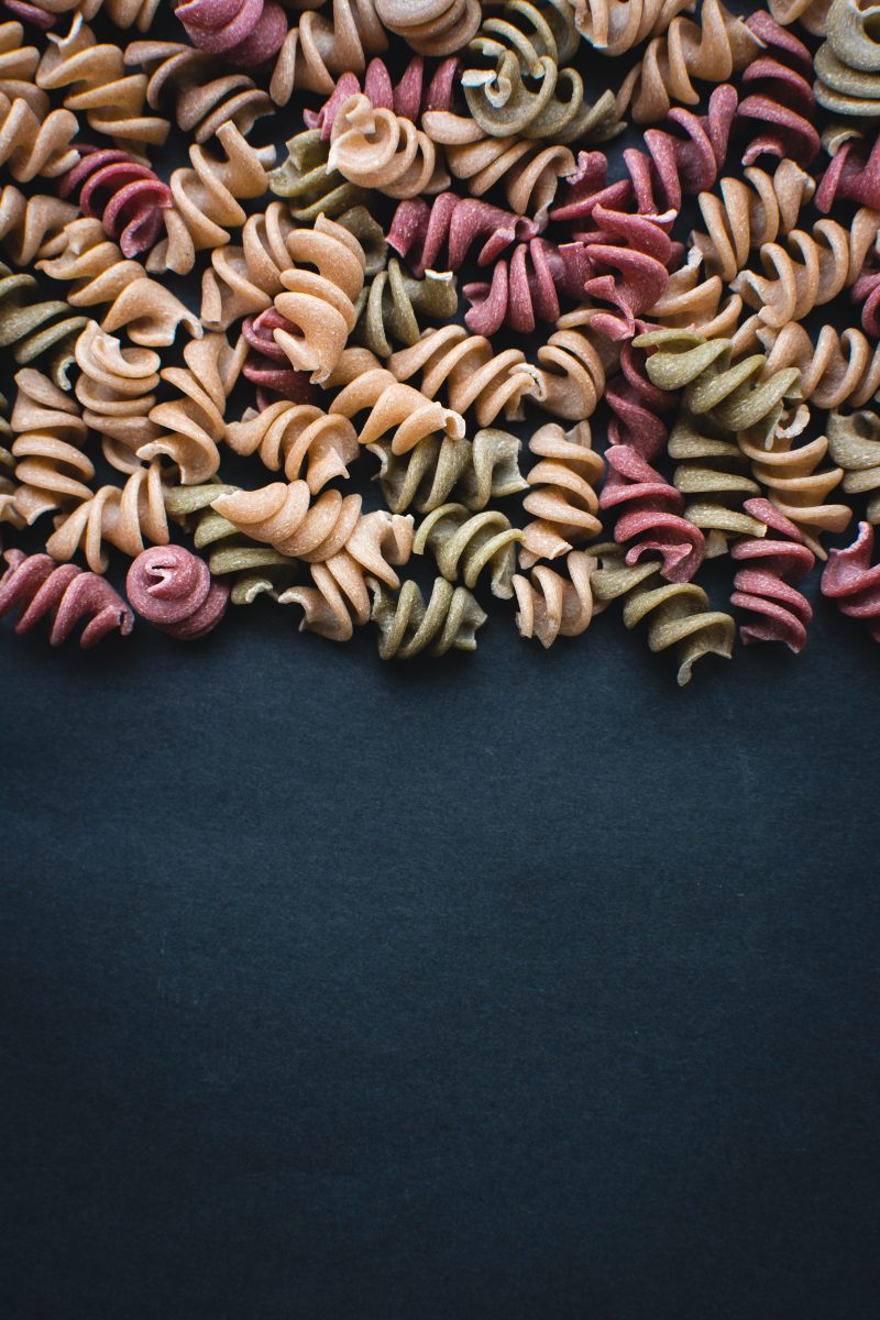 Colorful pasta fusilli on a black background