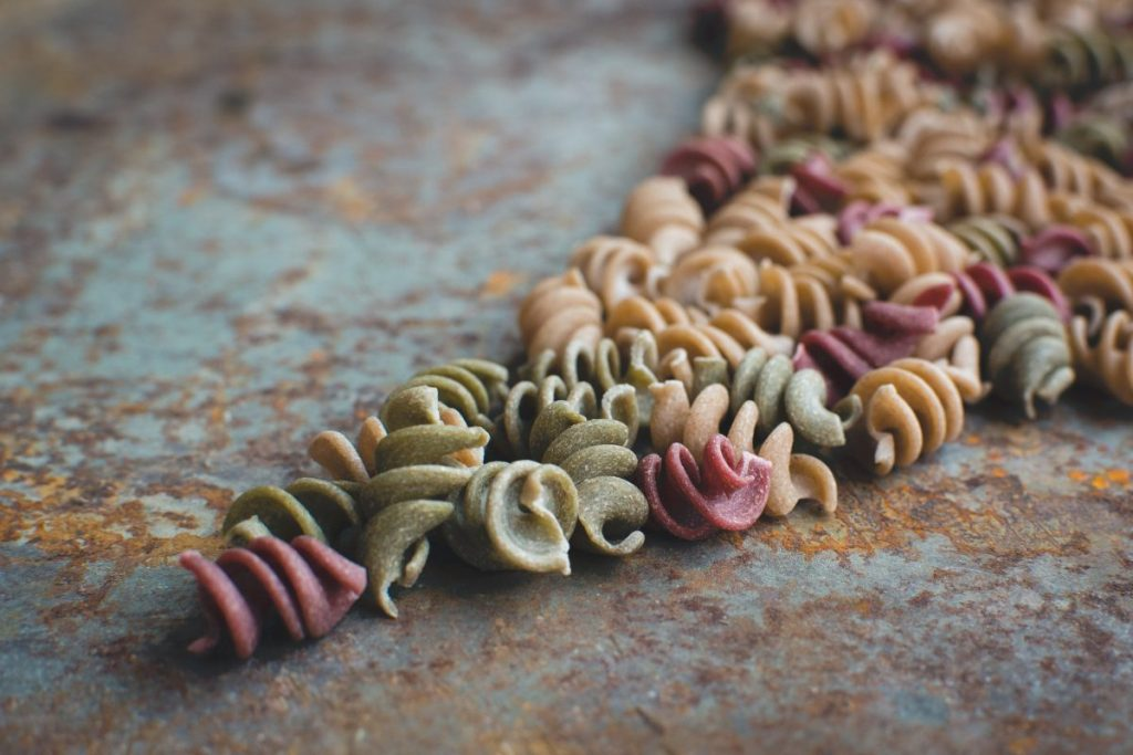 Colorful pasta fusilli on a rusty metallic background