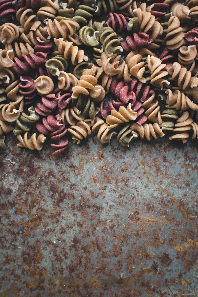 Colorful pasta fusilli on a rusty metallic background