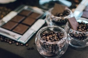 Dark chocolate bar and coffee beans in glasses