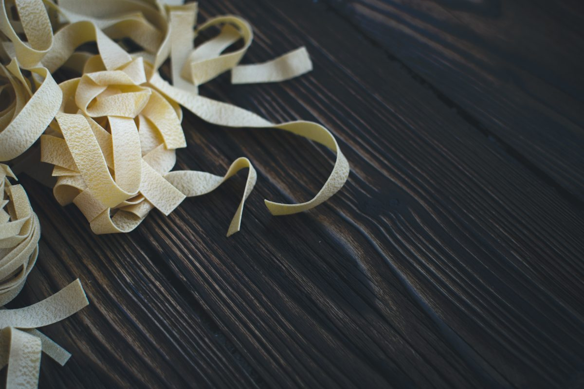 Detail of pasta tagliatelle on a wooden background