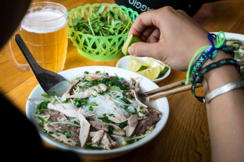 Eating Vietnamese Pho soup with fresh lime