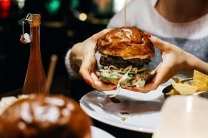 Girl holding a juicy beef burger