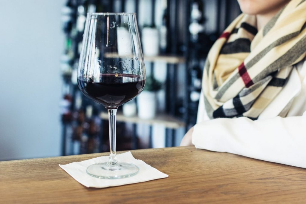 Lady drinking her glass of red wine in a wine shop