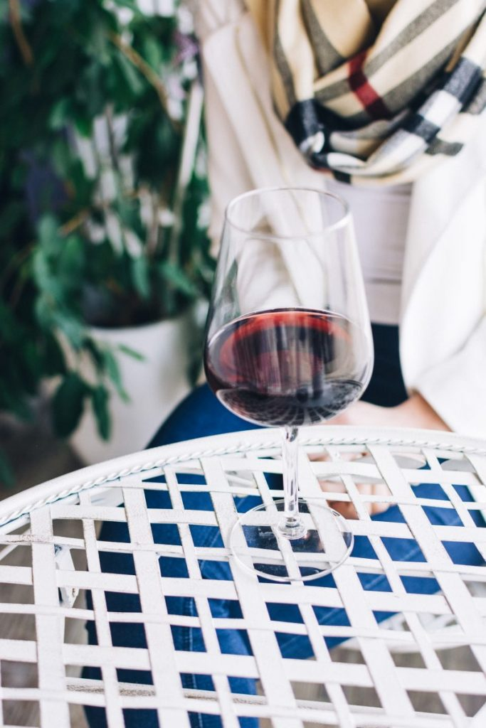 Lady with a glass of red wine in a wine shop