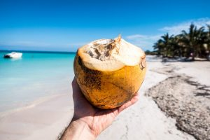 Drinking fresh young coconut on the beach