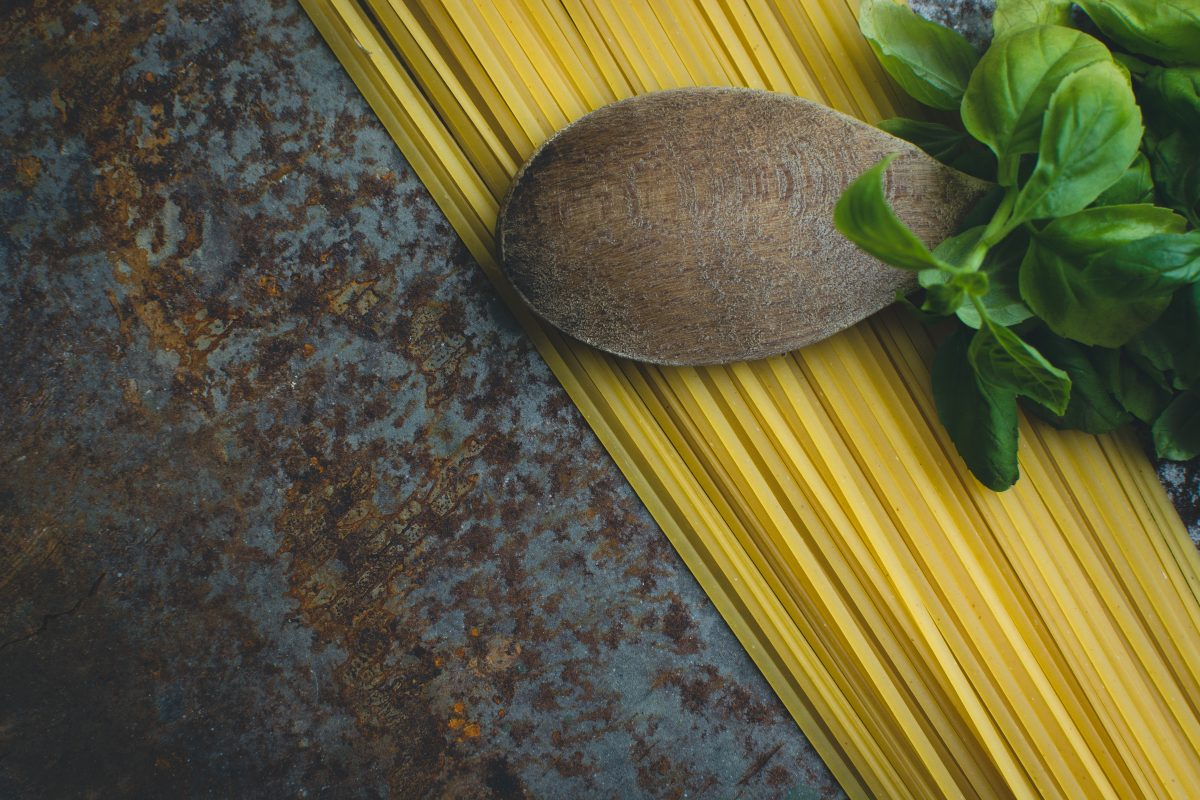 Pasta spaghetti with basil and wooden spoon on a rusty metallic background