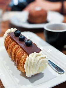 Creme roll with chocolate and blueberries on top