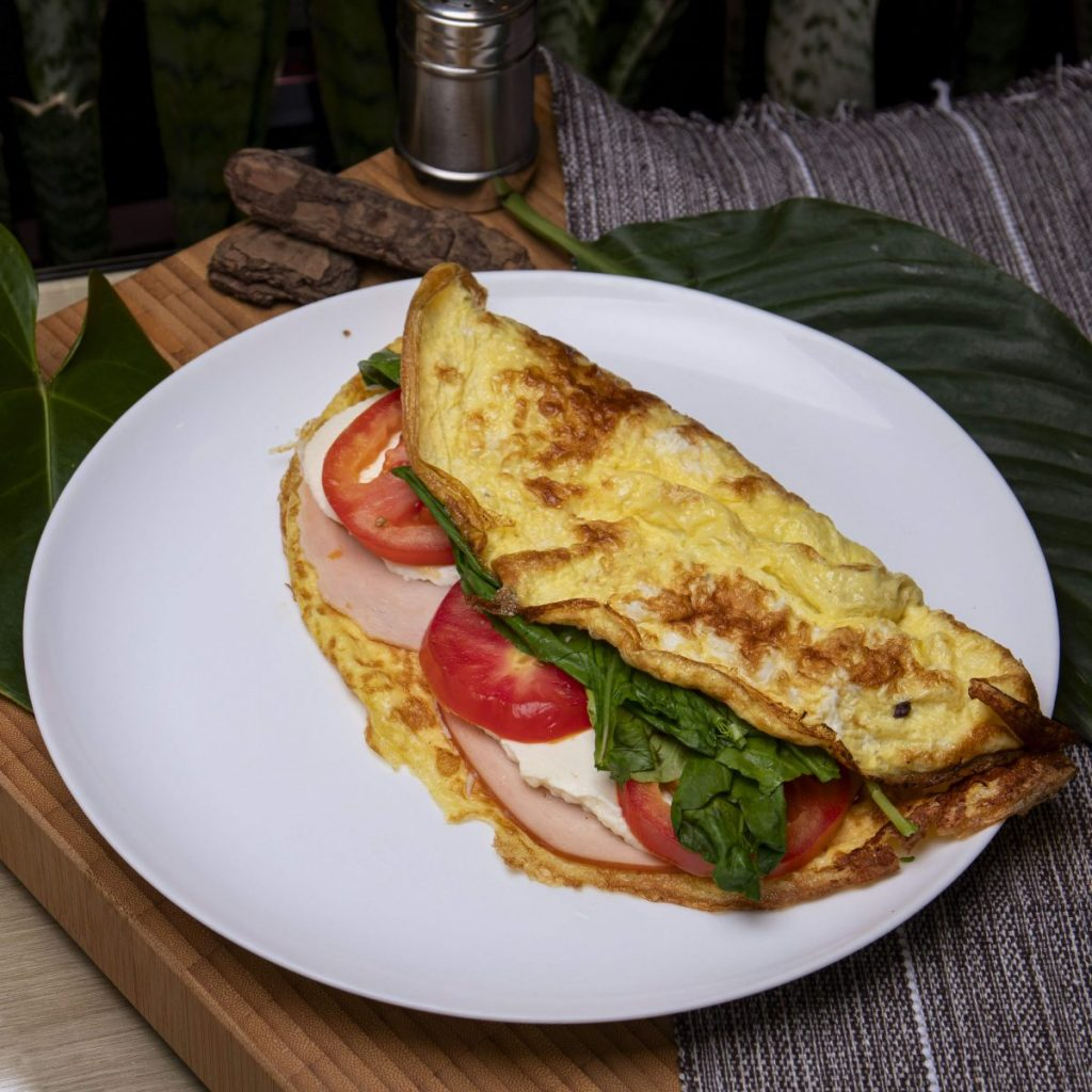Homemade omelet with ham, cheese, spinach and tomatoes