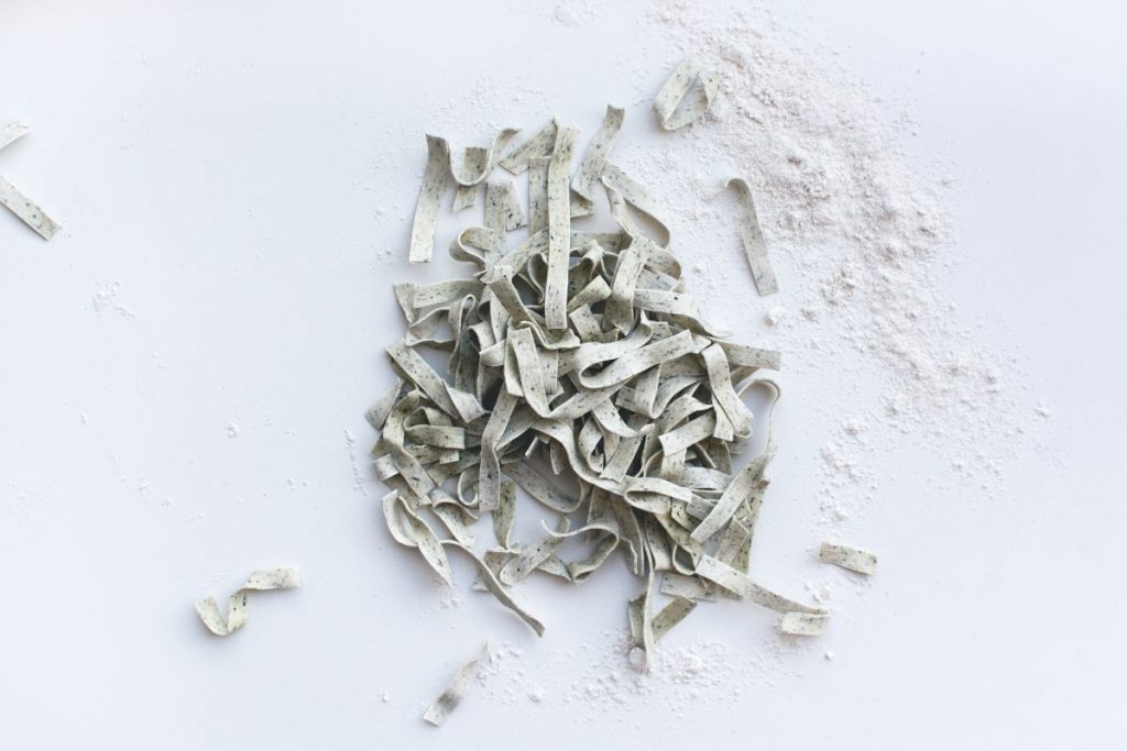 Pasta tagliatelle covered by flour on a white background
