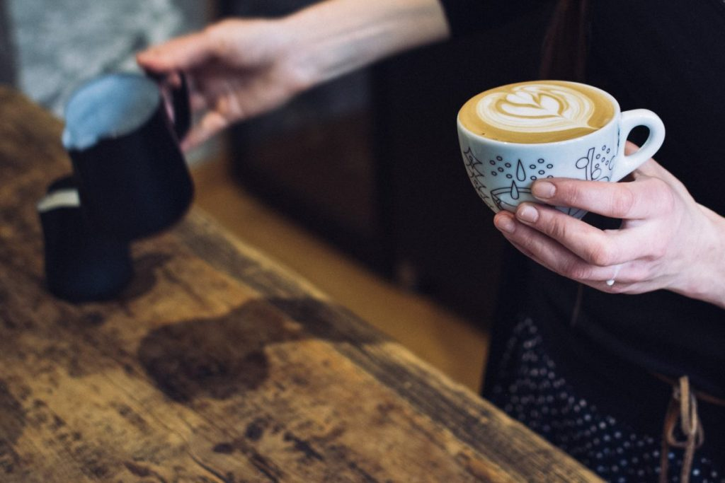 Barista holding a cup with coffee cappuccino