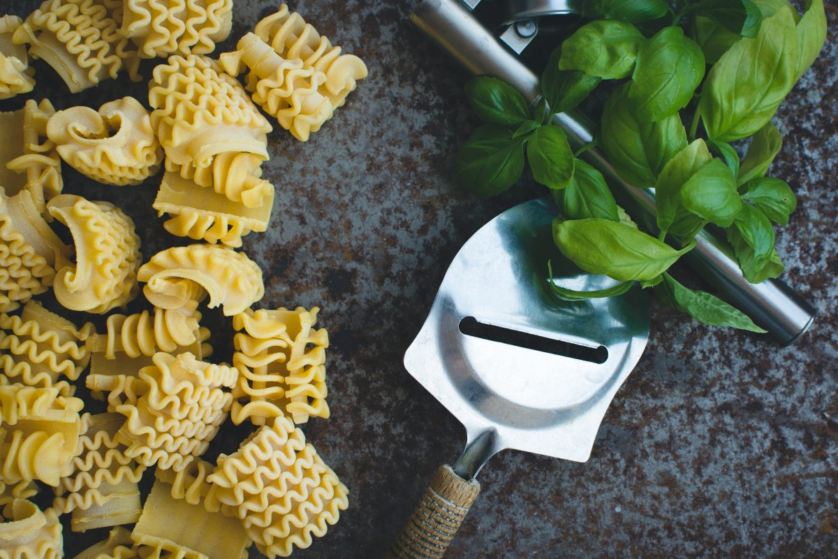 Pasta with a cheese grater and basil on a rusty metallic background