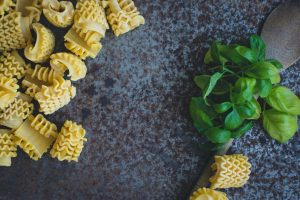 Pasta with basil and wooden spoon on a rusty metallic background
