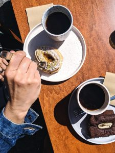 Aerial shot of a girl enjoying her coffee and dessert break