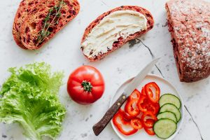 Preparing sandwich with hummus spread and fresh vegetables