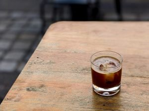 Cold coffee americano with ice cube on a wooden table